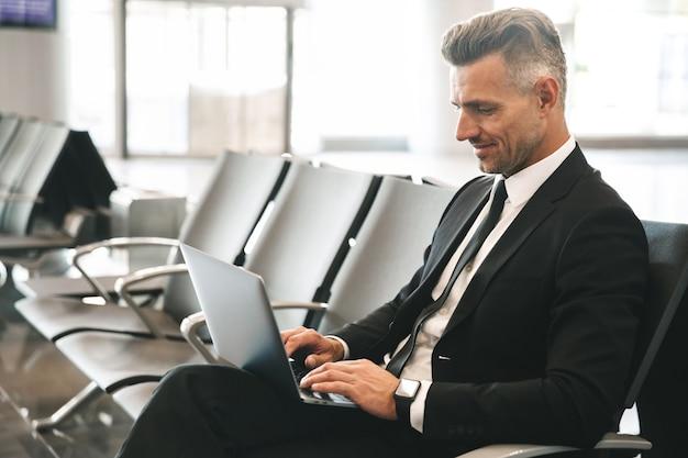 Lächelnder geschäftsmann, der laptop-computer benutzt