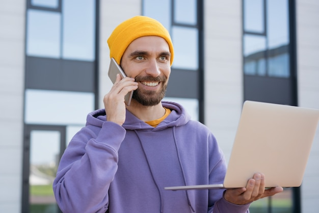 Lächelnder geschäftsmann, der laptop-computer verwendet, der auf handy spricht