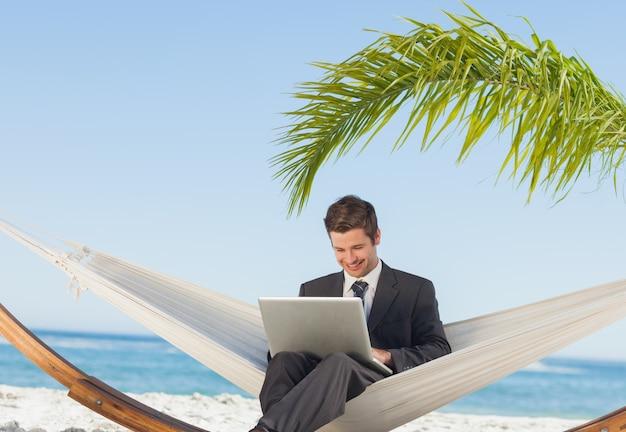 Lächelnder geschäftsmann, der laptop verwendet und in der hängematte sitzt