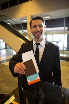 Lächelnder geschäftsmann, der seine bordkarte zeigt