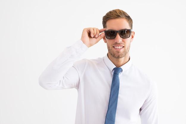 Lächelnder geschäftsmann, der sonnenbrille justiert und kamera betrachtet