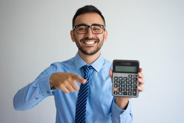 Lächelnder geschäftsmann, der taschenrechner zeigt