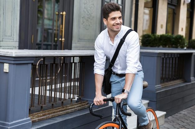 Lächelnder geschäftsmann gekleidet im hemd, das auf einem fahrrad reitet
