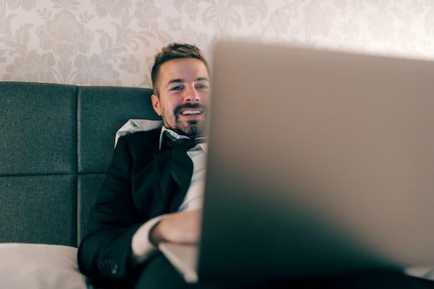 Lächelnder geschäftsmann im anzug, der nachts auf dem bett im hotelzimmer liegt und laptop für arbeit benutzt. überarbeitendes konzept.