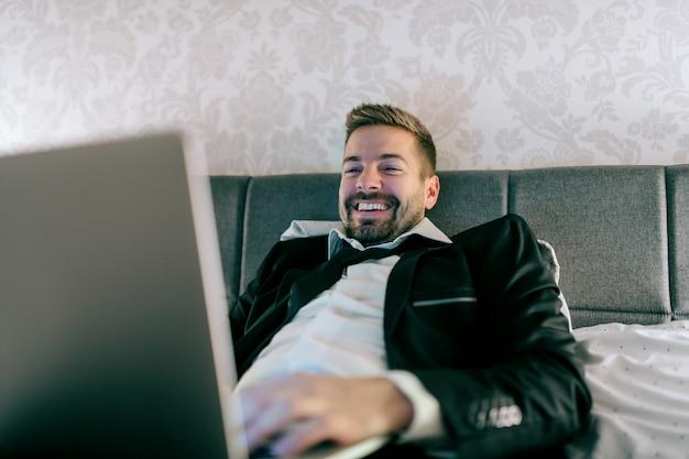 Lächelnder geschäftsmann im anzug, der nachts auf dem bett im hotelzimmer liegt und laptop für arbeit benutzt.