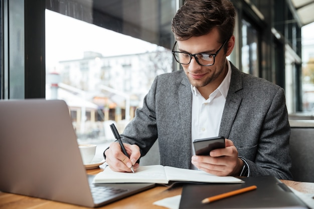 Lächelnder geschäftsmann in den brillen, die durch die tabelle im café mit laptop-computer bei der anwendung des smartphone und beim schreiben etwas sitzen