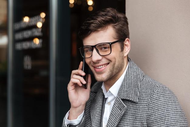Lächelnder geschäftsmann in den brillen und in mantel sprechend durch smartphone