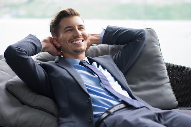 Lächelnder geschäftsmann mit den händen hinter dem kopf auf sofa