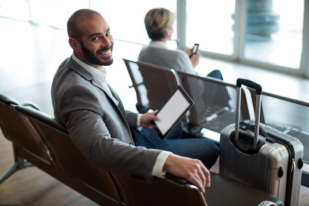 Lächelnder geschäftsmann mit der digitalen tablette, die im wartebereich sitzt