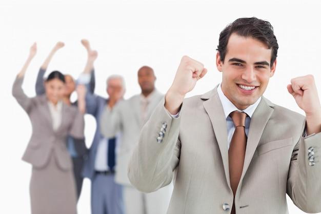 Lächelnder geschäftsmann mit team hinter ihm fäuste anhebend