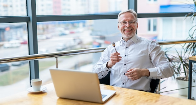 Lächelnder geschäftsmann mittleren alters im weißen hemd mit einem laptop. mann sitzt am fenster und arbeitet mit dokumenten.