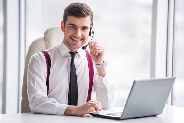 Lächelnder geschäftsmann nimmt einen anruf auf einem kopfhörer entgegen.