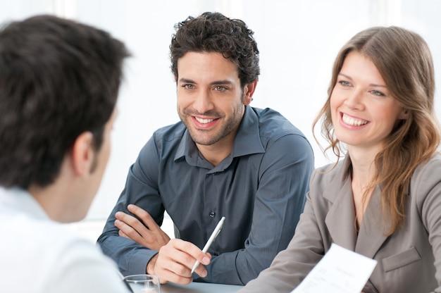 Lächelnder geschäftsmann und kollegen, die zusammen an dokumenten im büro arbeiten