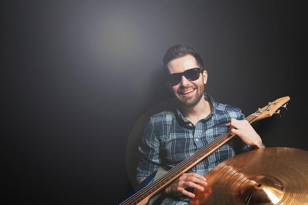 Lächelnder gitarrist auf schwarzem hintergrund