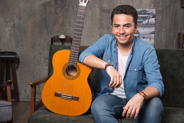 Lächelnder gitarrist, der eine schöne gitarre hält und auf sofa sitzt. hochwertiges foto