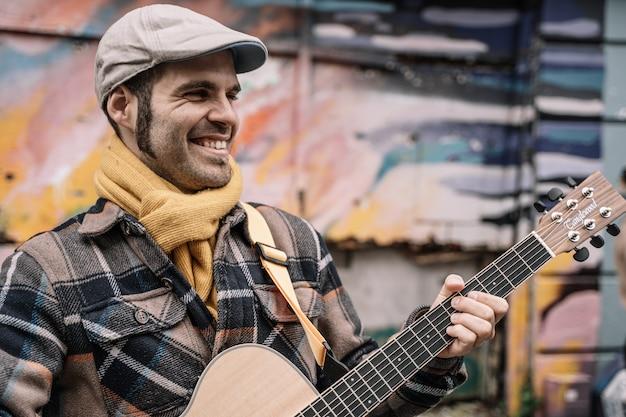 Lächelnder gitarristmann, der auf der straße spielt