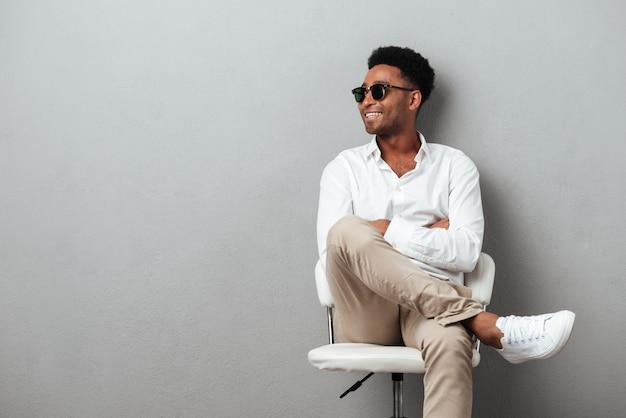 Lächelnder glücklicher afrikanischer mann, der in einem stuhl aufwirft