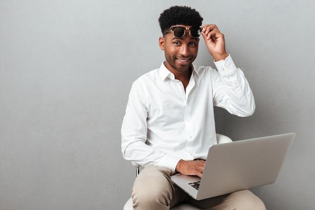 Lächelnder glücklicher afrikanischer mann, der laptop-computer auf seinem schoß hält
