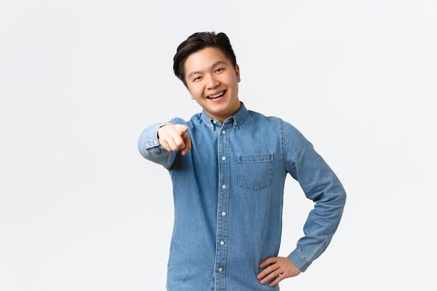 Lächelnder glücklicher asiatischer gutaussehender kerl im blauen hemd, hat klammern, zeigt mit dem finger auf die kamera, ermutigt die person, auf den link zu klicken, jemanden zu benennen oder auszuwählen, der auf weißem hintergrund steht.