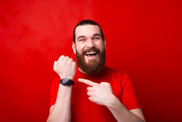 Lächelnder glücklicher bärtiger mann, der auf rot steht und auf smartwatch zeigt