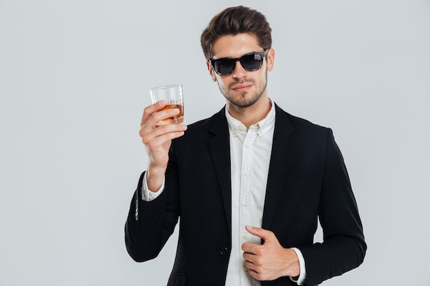 Lächelnder glücklicher geschäftsmann im anzug, der ein glas whisky über grauer wand hält