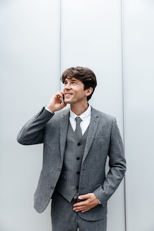 Lächelnder glücklicher geschäftsmann im anzug, der ein handygespräch hat