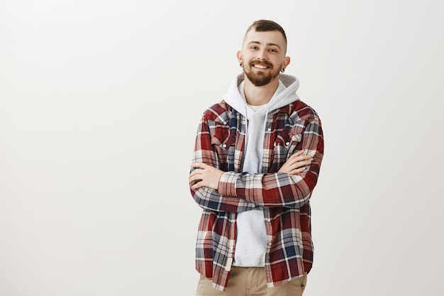 Lächelnder glücklicher hipster-typ verschränkt selbstbewusst die arme auf der brust