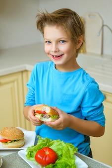 Lächelnder glücklicher junge, der hausgemachte hamburger oder sandwiches hält