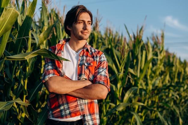 Lächelnder glücklicher junger agronom oder bauer, der rotes kariertes hemd trägt