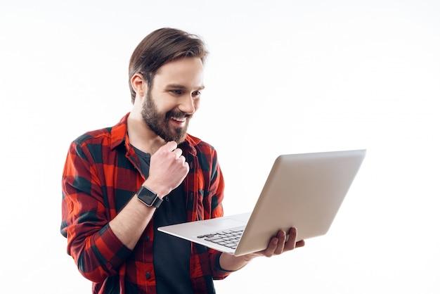 Lächelnder glücklicher junger bärtiger kerl, der an laptop arbeitet