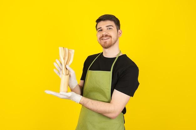 Lächelnder glücklicher junger mann, der küchenwerkzeuge hält und kamera betrachtet.