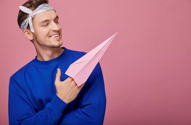 Lächelnder glücklicher kerl in der dunkelblauen strickjacke des weißen bandanins mit rosa papierflugzeug in der hand