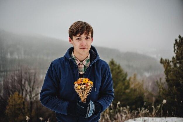 Lächelnder glücklicher mann mit bündel trockener gelber blumen im winterpark. frauentag.