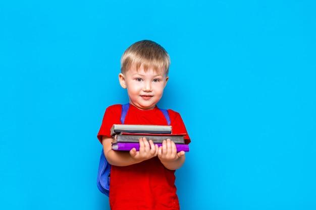 Lächelnder glücklicher netter kluger junge mit rucksack. kind mit einem stapel bücher in seinen händen. fertig für die schule. zurück zur schule