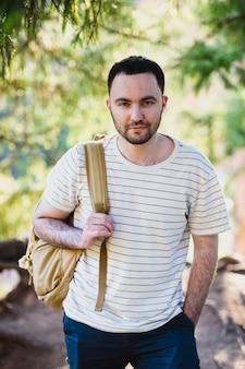 Lächelnder glücklicher schöner mann mit bart im wald, in den bergen, im park. traveller man entspannt. travel lifestyle wanderkonzept sommerferien im freien.