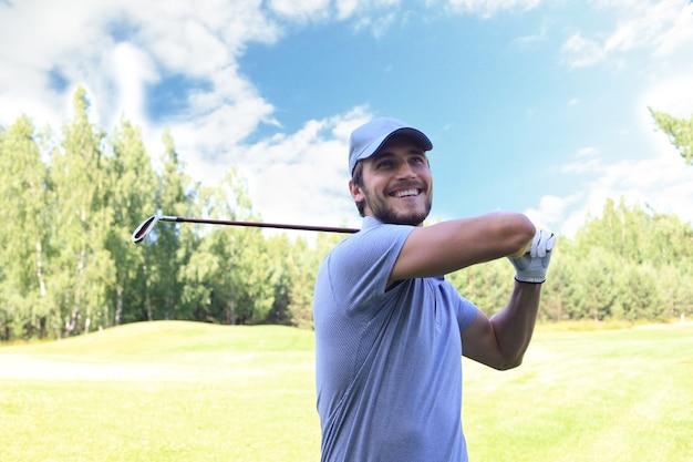 Lächelnder golfer, der im sommerurlaub golf mit schläger auf kurs schlägt.