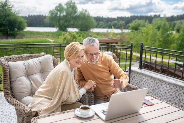 Lächelnder grauhaariger mann mit brille und seine fröhliche ehefrau, die während des videoanrufs auf den laptop schaut