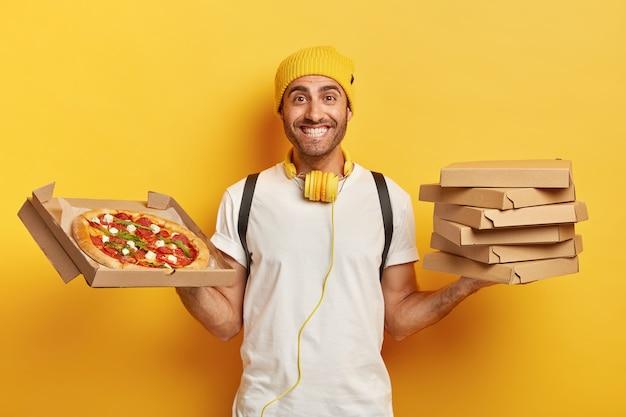 Lächelnder gut aussehender lieferbote mit pizzaschachteln