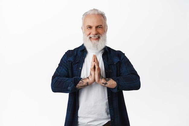 Lächelnder gutaussehender älterer mann, der händchen in der namaste-geste hält, sich bedankt, hilfe schätzt, dankbar und glücklich aussieht und über weißer wand steht