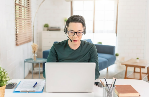 Lächelnder gutaussehender asiatischer geschäftsmann, der von zu hause aus arbeitet. er ist webinar-videokonferenz.