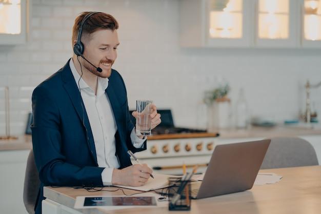Lächelnder gutaussehender geschäftsmann im anzug, der im headset sitzt und eine webkonferenz auf dem laptop hat, während er zu hause arbeitet, männlicher freiberufler mit einem glas wasser in der hand, der auf den computerbildschirm schaut und lächelt