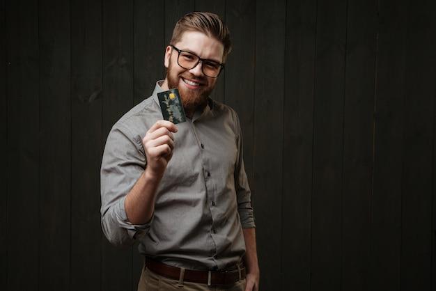 Lächelnder gutaussehender geschäftsmann mit brille, der die kreditkarte in der hand hält und die vorderseite isoliert auf der schwarzen holzoberfläche betrachtet