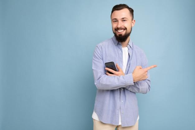 Lächelnder gutaussehender junger, brünetter, unrasierter mann mit bart, der ein stylisches weißes t-shirt und ein blaues hemd trägt, isoliert auf blauem hintergrund mit leerem raum, der in der hand hält und in die kamera schaut