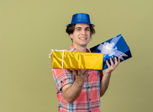 Lächelnder gutaussehender kaukasischer mann mit blauem partyhut hält geschenkboxen