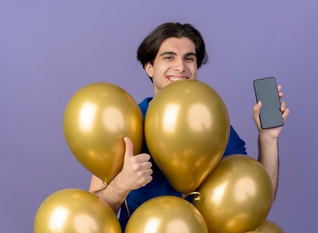Lächelnder gutaussehender kaukasischer mann steht mit heliumballons daumen hoch und hält telefon
