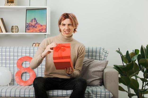 Lächelnder, gutaussehender kerl am glücklichen frauentag, der das geschenk auf dem sofa im wohnzimmer hält