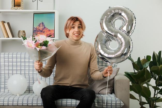 Lächelnder gutaussehender kerl am glücklichen frauentag, der den ballon nummer acht und den blumenstrauß auf dem sofa im wohnzimmer hält