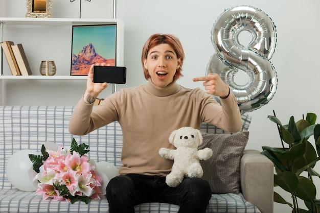 Lächelnder gutaussehender kerl am glücklichen frauentag hält und zeigt auf teddybär mit telefon, das auf dem sofa im wohnzimmer sitzt