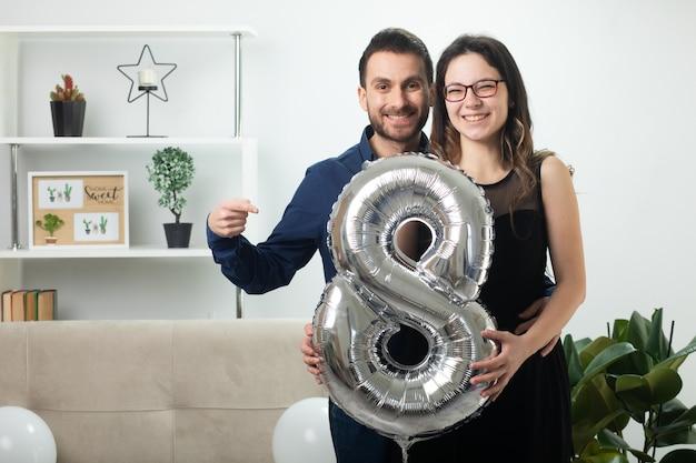 Lächelnder gutaussehender mann, der auf eine fröhliche hübsche junge frau in optischer brille zeigt, die am internationalen frauentag im märz eine ballonförmige acht im wohnzimmer hält
