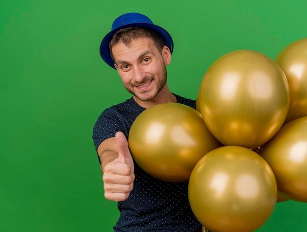 Lächelnder gutaussehender mann, der blauen parteihut trägt, hält heliumballons und daumen hoch lokalisiert auf grüner wand mit kopienraum